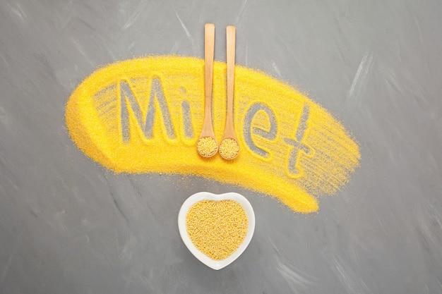 Napis proso z łuskanej mąki jaglanej na szarym tle drewniana łyżka i miska w kształcie serca