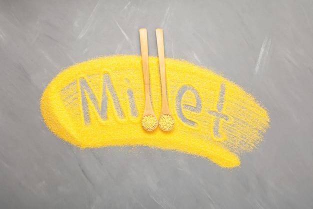 Napis proso z łuskanej mąki jaglanej na szarym tle żółte ziarno w drewnianych łyżkach widok z góry
