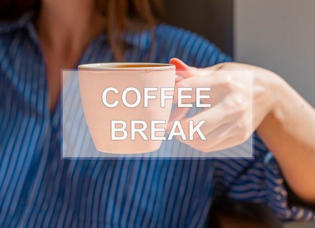 Napis przerwy na kawę na zdjęciu z ręką trzymającą filiżankę kawy
