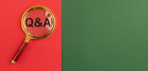 Napis qna na czerwono-zielonym sztandarze przez szkło powiększające. akronim kontroli jakości. koncepcja q. pytania i odpowiedzi. tło z miejsca na kopię.