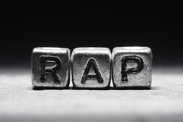 Napis rap na metalowych kostkach w stylu grunge na czarnym tle na białym tle