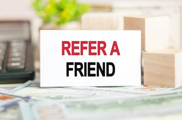 Napis refer a friend jest zapisany na białej karcie papierowej obok drewnianej kostki, kalkulatora na ścianie z banknotami. koncepcja biznesowa i finansowa