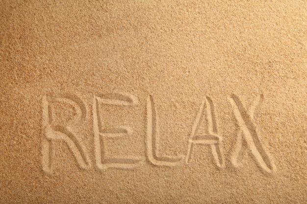 Napis relaks w piasku na tropikalnej wyspie.