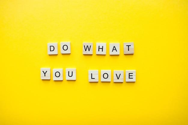 Napis rób to, co kochasz, z drewnianych klocków na jasnożółtym tle