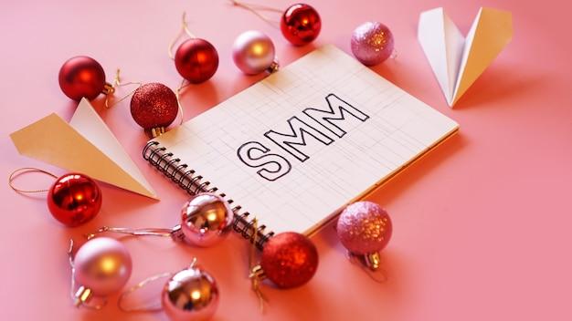 Napis smm w notatniku na różowym świątecznym tle. czerwone i różowe bombki, dookoła papierowe samoloty