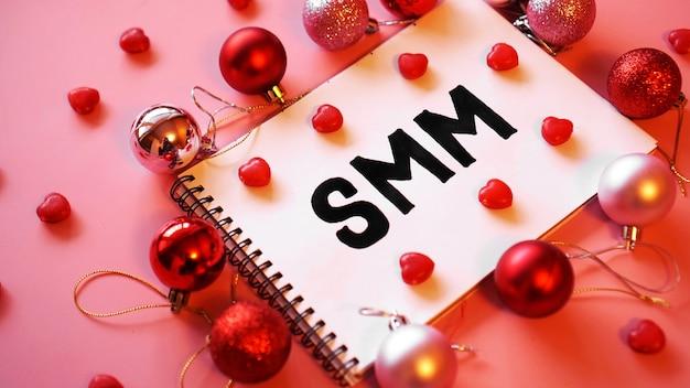 Napis smm w notatniku na różowym świątecznym tle. czerwono-różowe bombki i cukierki w formie serc