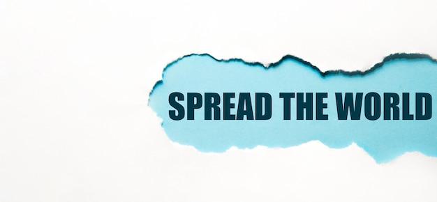 Napis spread the world na podartym papierze, jasne rozwiązanie dla biznesu, finansów