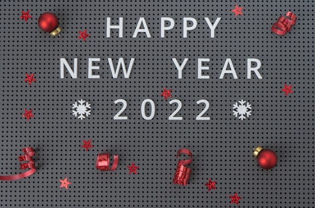 Napis szczęśliwego nowego roku 2022 na szarym tle z czerwonymi ozdób choinkowych, konfetti