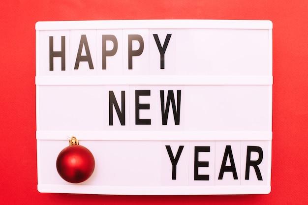 Napis szczęśliwego nowego roku na podświetlanym pudełku z bożonarodzeniową piłką zabawkową na czerwonym tle