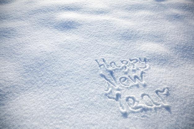 Napis szczęśliwego nowego roku na tle śnieżnej zimy