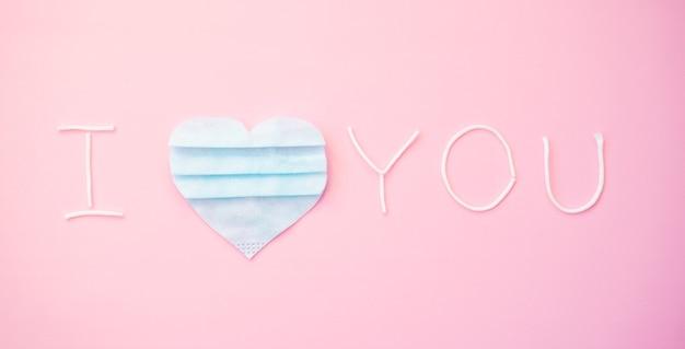 Napis, tekst i love you z niebieskim sercem, wycięty z kawałków używanej medycznej maski na twarz.