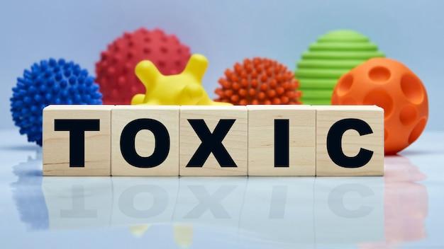 Napis toxic na drewnianych kostkach i różnych formach wirusów