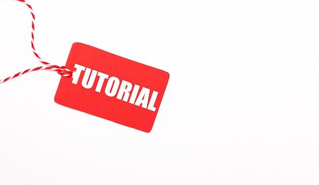 Napis tutorial na czerwonej metce na jasnym tle. koncepcja reklamy. skopiuj miejsce