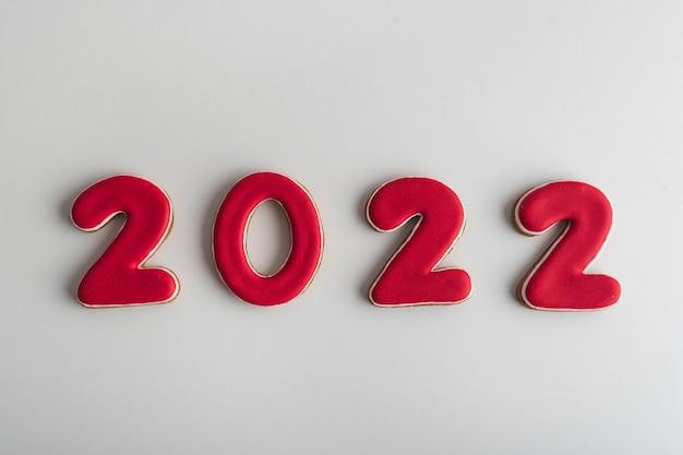 Napis w czerwonych cyfrach 2022 z piernika na białym tle. szczęśliwego nowego roku 2022