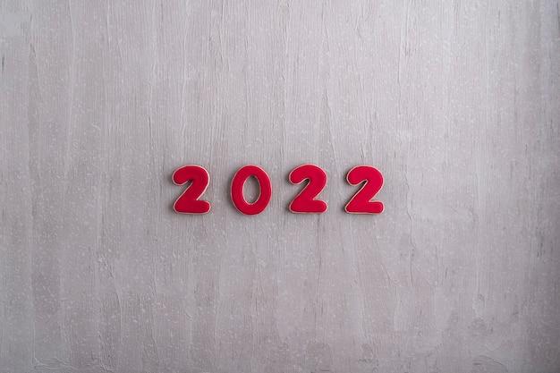 Napis w czerwonych cyfrach 2022 z piernika na szarym tle. nowy rok 2022
