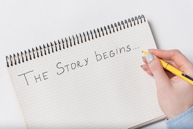 Napis w zeszycie zaczyna się historia. ręka pisze w zeszycie. słowa odręcznie.