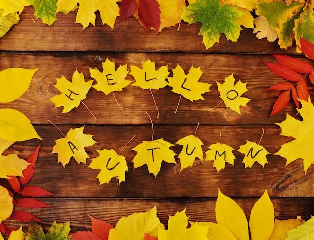 Napis witaj jesień na żółtych liściach klonu na drewnie