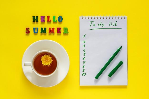 Napis witaj lato, filiżanka herbaty z mniszka lekarskiego, lista rzeczy do zrobienia, długopis