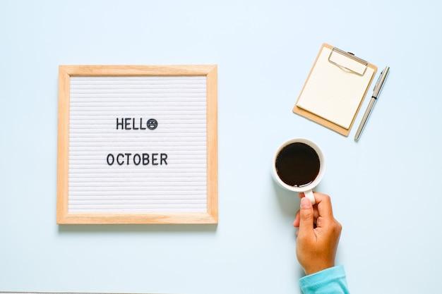 Napis witam października na białej tablicy z suchymi liśćmi na jasnoniebieskim tle. jesienna koncepcja