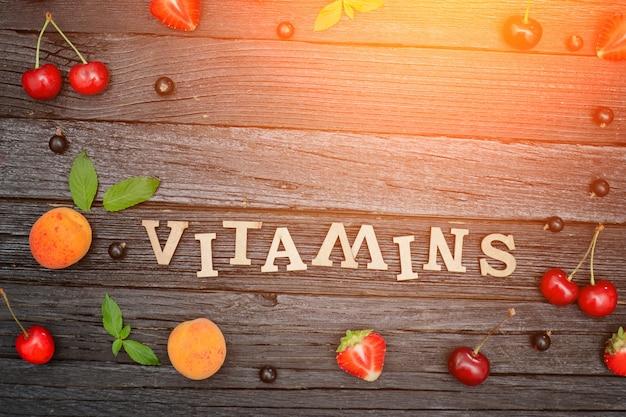 Napis witaminy i owoce. czarne drewniane tła. koncepcja żywności