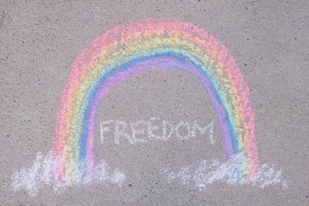 Napis wolność i tęcza narysowana kredą na asfalcie, symbol społeczności lgbt, kredki na ziemi widok z góry