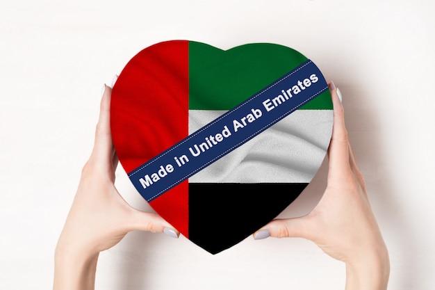 Napis wykonany w zjednoczonych emiratach arabskich flaga zjednoczonych emiratów arabskich. kobiece ręce trzyma pudełko w kształcie serca. biały