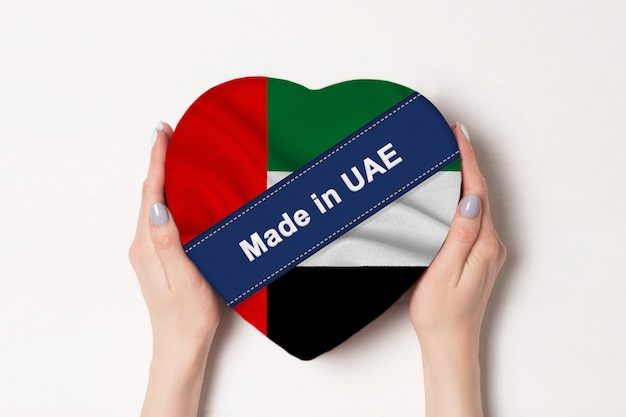 Napis wykonany w zjednoczonych emiratach arabskich flaga zjednoczonych emiratów arabskich. kobiece ręce trzyma pudełko w kształcie serca