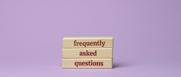 Napis z często zadawanymi pytaniami na drewnianych klockach na fioletowej powierzchni