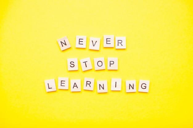 """Napis z drewnianych klocków """"nigdy nie przestawaj się uczyć"""" na jasnożółtym tle"""