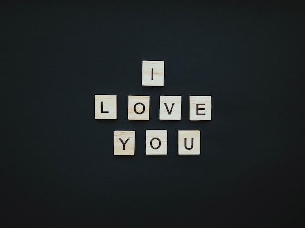 Napis z drewnianych kwadracików kocham cię na pięknym czarnym tle. romantyczna koncepcja. płaski styl.