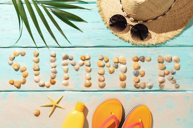 Napis z muszelek i akcesoriów plażowych na kolorowym tle