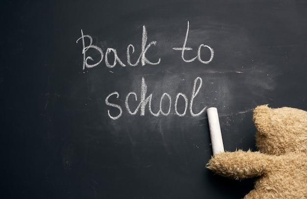 Napis z powrotem do szkoły białą kredą na czarnej tablicy szkolnej