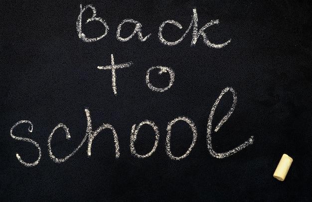 Napis z powrotem do szkoły na czarnej tablicy, z bliska.