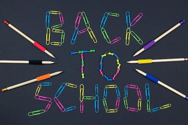Napis z powrotem do szkoły na tablica tło wykonane z kolorowych spinaczy