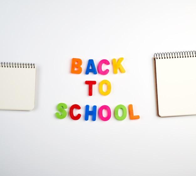 Napis z powrotem do szkoły z wielokolorowych plastikowych liter i stosu zeszytów z pustymi białymi kartkami