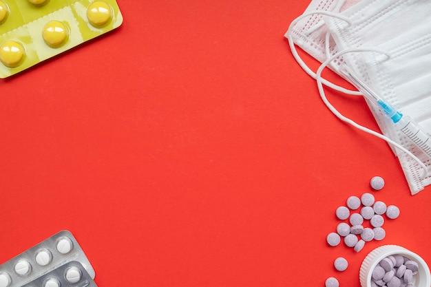 Napis zatrzymać koronawirusa. pigułki i medycyn maski na czerwonym tle. widok z góry, miejsce na tekst