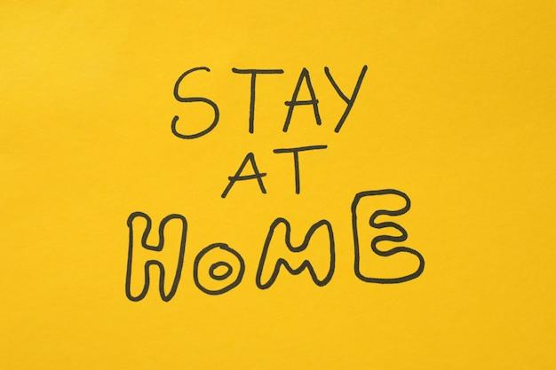 Napis zostań w domu na żółtej powierzchni. kwarantanna