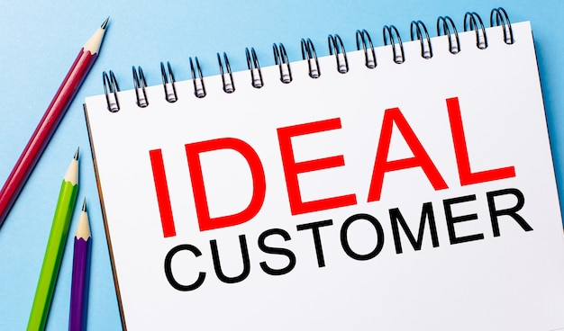 Napisz idealny klient na białym notatniku z ołówkami na niebieskim polu
