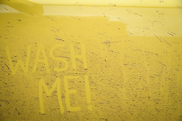 Napisz słowa napis tekst umyj mnie na bardzo brudnej powierzchni samochodu. myjnia samochodowa koncepcyjna.