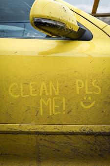 """Napisz tekst napisu """"oczyść mnie"""" na bardzo brudnej powierzchni samochodu. myjnia samochodowa koncepcyjna."""