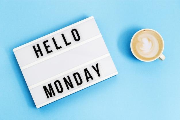 """Napisz """"witaj w poniedziałek"""" na lightboxie i filiżance kawy na wakacje. początek koncepcji tygodnia roboczego. widok z góry na niebieskim tle."""