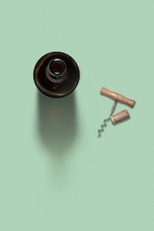 Napój alkoholowy butelka wina z naturalnym korkiem i korkociągiem na jasnozielonym tle z miękkimi cieniami i przestrzenią do kopiowania. widok z góry.