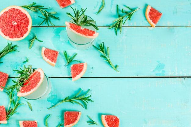 Napój alkoholowy, rozmaryn, grejpfrut i koktajl z dżinu, na jasnoniebieskim drewnianym stole, widok z góry