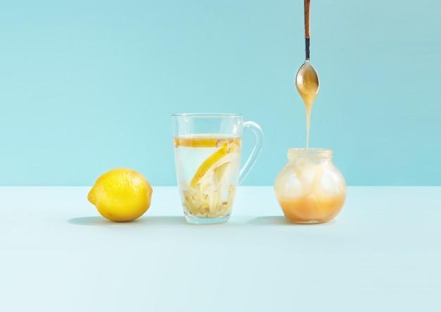 Napój antywirusowy w szklanej filiżance z cytryną, imbirem i miodem na niebieskim cyjanie