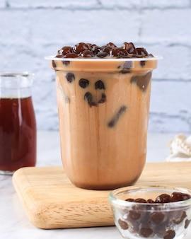 Napój bąbelkowy z brązowym cukrem. plastikowy kubek świeżego mleka i dodatków typu boba/bąbelki z brązowego cukru. udekoruj liściem mięty