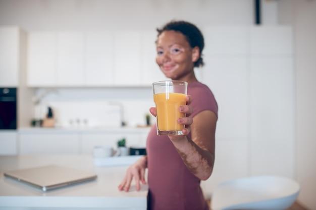 Napój cytrusowy. ciemnoskóra kobieta trzymająca szklankę soku pomarańczowego