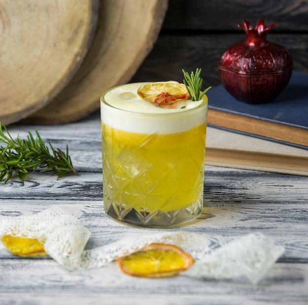 Napój cytrynowy przyozdobiony suszonym plasterkiem cytryny, rozmarynem w szkle kryształowym