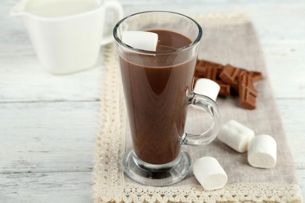 Napój czekoladowy z piankami w kubku, na drewnianym stole