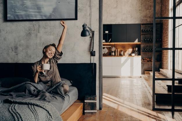 Napój energetyczny. młoda piękna pozytywna europejska kobieta siedzi na łóżku, rozciągając się z ręką w górę, trzymając filiżankę kawy drugą ręką, próbując obudzić się przed pójściem rano pod prysznic