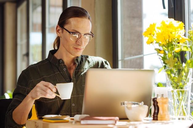 Napój energetyzujący. przyjemny długowłosy mężczyzna trzymający filiżankę z espresso, patrząc na ekran laptopa